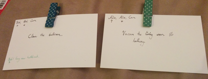 Two pieces of card each with one chore.  The first has a note 'Alice, Alice, Cara' in the top left.  The second has a note 'Bob, Bob, Cara' in the top left.